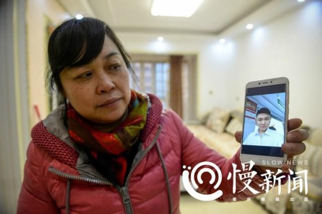 Bà He Xiaoping khoe ảnh Liu Jinxin, người con trai bà đã bắt cóc và nuôi nấng 26 năm. Ảnh: Sina.