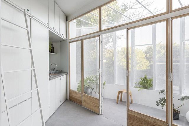 Cửa kép bằng kính và gỗ sáng màu ngăn cách khu vực sinh hoạt bên trong với ban công.