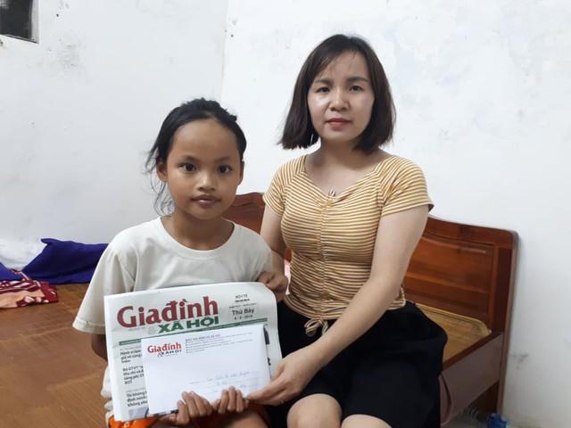 Phóng viên Phương Thuận đại diện chương trình Vòng tay nhân ái trao tiền cho em Quỳnh. Ảnh T
