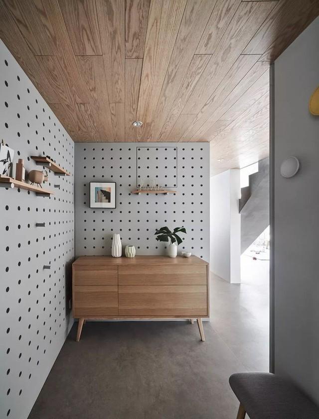Không gian đặc biệt hơn nhờ điểm nhấn tủ giày màu gỗ trên nền ghi trung tính.