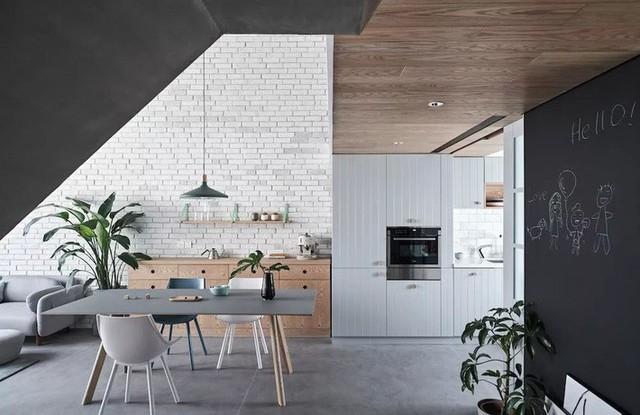 Góc bếp được kết nối với khu vực ăn uống bằng màu ghi. Thêm màu gỗ của trần kết hợp tủ bếp để tăng thêm nét ấm cúng, tự nhiên.