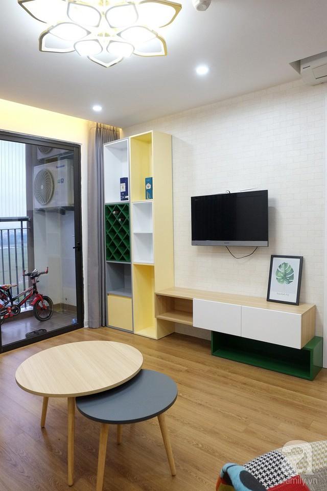 Khu vực tường tivi được nối liền bởi kệ tivi và kệ trang trí dạng đứng ngay cạnh ban công. Để tạo vẻ đẹp ấn tượng cho khu vực này, các KTS đã chọn giấy dán tường vân gạch màu trắng nhẹ nhàng.