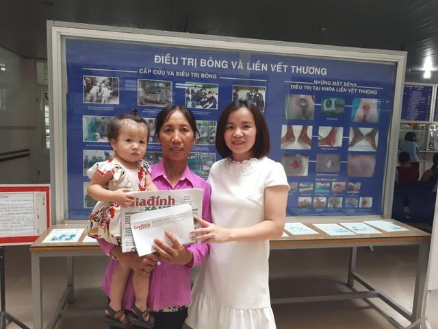 Phóng viên Phương Thuận - đại diện Chương trình Vòng tay nhân ái trao tiền cho gia đình bé Nhi.