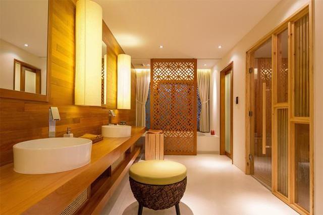 Phòng tắm rộng thênh thang mang phong cách thiền định với vách trang trí gỗ kết hợp với chất liệu vải của màn và đèn vàng.
