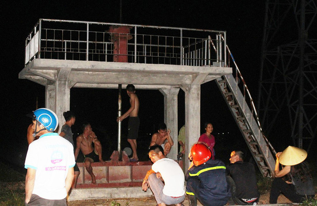 Người dân và lực lượng cứu hộ ngồi dưới cột điện trong đêm