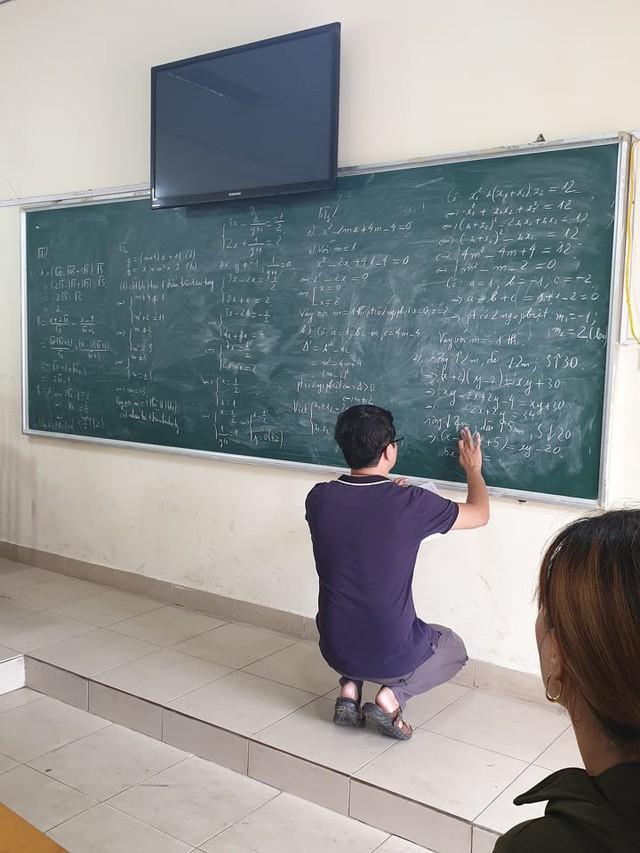 Thầy giáo Phạm Đình Phước đang chữa bài cho học trò của mình sau khi tan thi