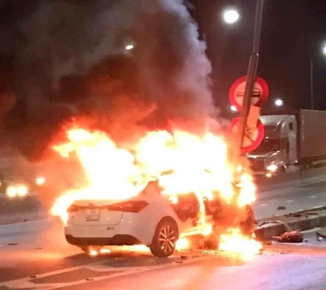 Sau khi đâm phải cột đèn tìn hiệu giao thông, chiếc xe ô tô bất ngờ bốc cháy. Ảnh: Bạn đọc cung cấp