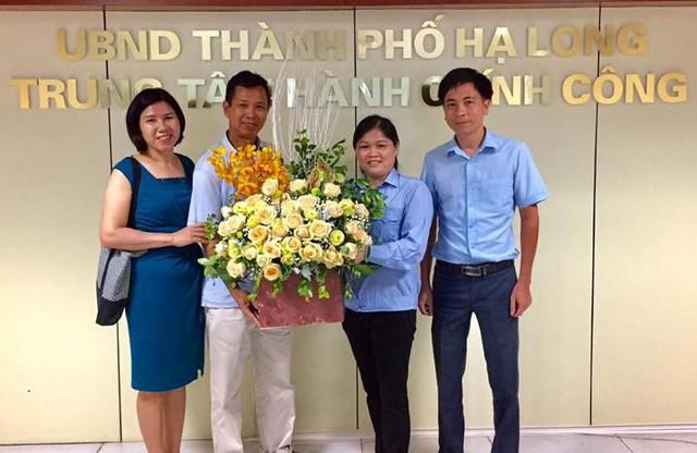 Chị Lịch nhận hoa cảm ơn của vợ chồng anh Tuấn sau khi nhặt được số tài sản bỏ quên tại Trung tâm Hành chính công TP. Hạ Long. Ảnh: Thu Hoài
