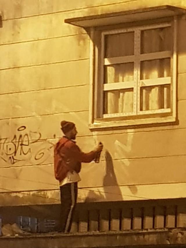 Người đàn ông mặc áo đỏ trèo lên nóc nhà Hồng Châu để vẽ lên tường.