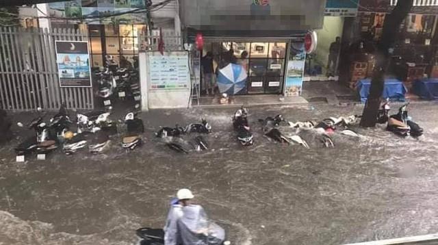 Hà Nội: Nhiều tuyến phố trung tâm bất ngờ ngập nặng, người dân vật lộn giữa mênh mông nước - Ảnh 1.