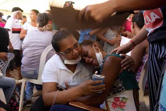 Thân nhân ngất xỉu nhận xác tù nhân bị chặt đầu sau bạo loạn ở Brazil - Ảnh 1.