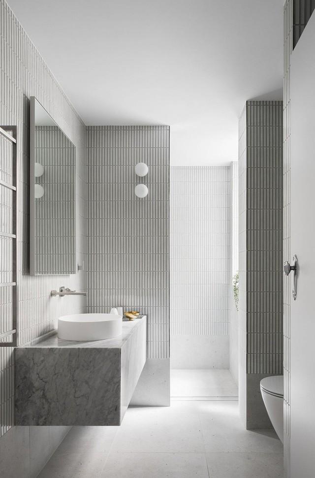 Phòng tắm màu xám và trắng với ánh sáng tự nhiên rộng rãi.