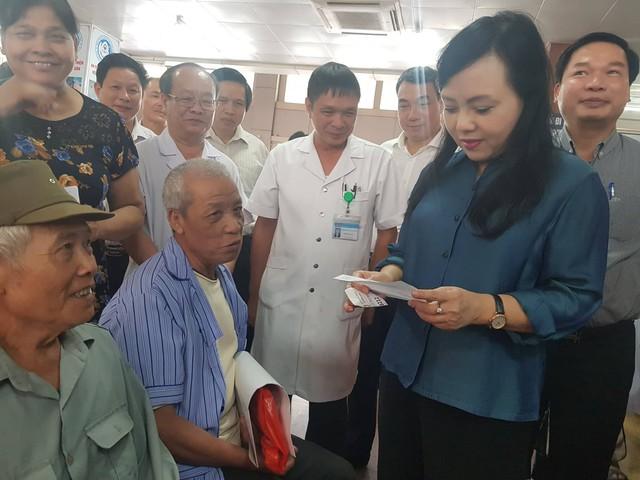 Trực tiếp kiểm tra đơn thuốc, sổ khám bệnh của người dân, Bộ trưởng Nguyễn Thị Kim Tiến mong muốn BVĐK tỉnh Ninh Bình nghiên cứu những biện pháp giúp giảm thời gian chờ đợi của người bệnh. Ảnh: Võ Thu