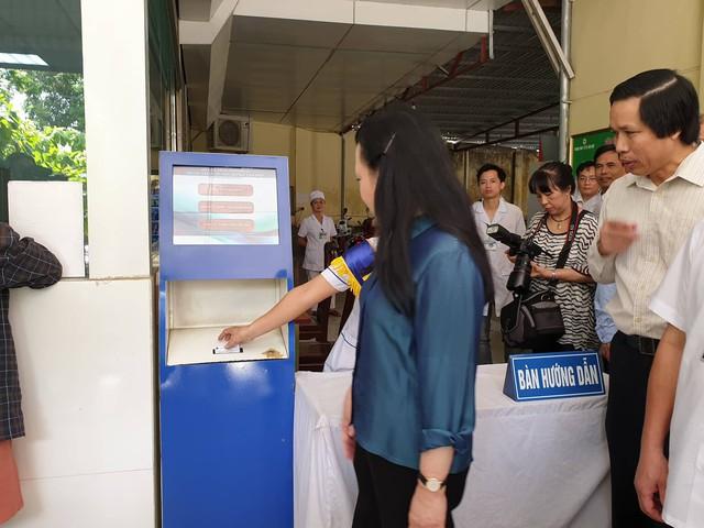 Bộ trưởng Y tế được nhân viên y tế hướng dẫn lấy số thứ tự điện tử...