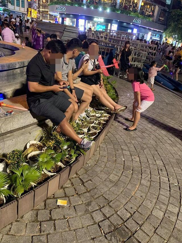 Bức xúc hình ảnh hàng chục người ngồi bên đài phun nước phố đi bộ Hồ Gươm, thản nhiên đạp chân thẳng lên hàng hoa trang trí - Ảnh 2.