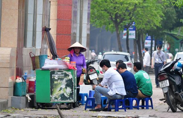 Nguy cơ COVID-19 đang cận kề nhưng nhiều người Hà Nội vẫn giữ thói quen túm năm tụm ba quán nước vỉa hè  - Ảnh 1.