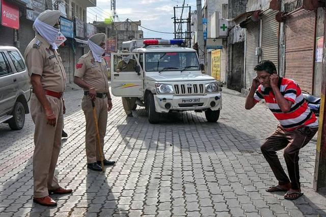 Ấn Độ trong ngày đầu phong tỏa 1,3 tỷ dân: Phạt ngồi xổm, đánh roi người vi phạm và muôn kiểu tránh xa nhau nơi công cộng - Ảnh 6.