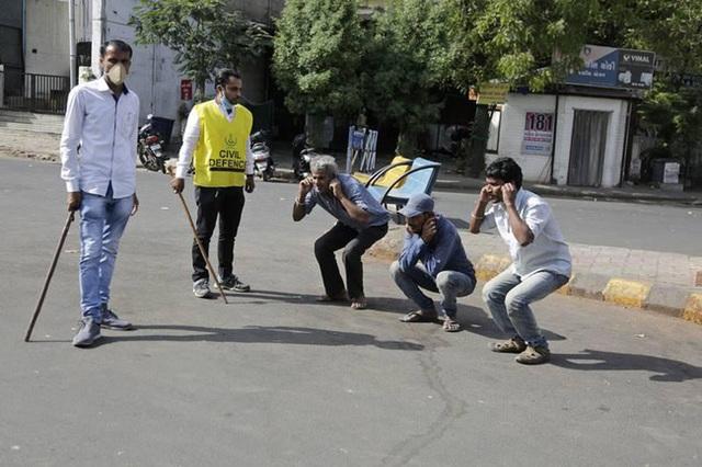 Ấn Độ trong ngày đầu phong tỏa 1,3 tỷ dân: Phạt ngồi xổm, đánh roi người vi phạm và muôn kiểu tránh xa nhau nơi công cộng - Ảnh 9.