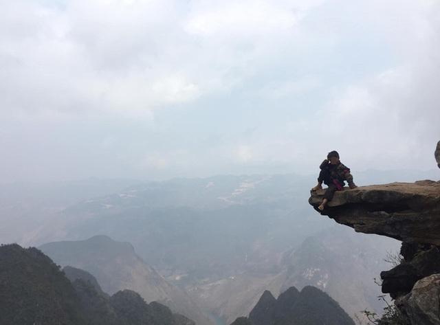 Hãi hùng cảnh 2 đứa trẻ vùng cao ngồi vắt vẻo trên mỏm đá, bên dưới là vực sâu nhưng nguyên nhân phía sau còn gây choáng váng hơn - Ảnh 2.