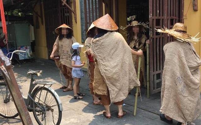 Lộ danh tính gây sốc của nhóm người ăn mặc lạ, đội nón lá, mang gậy, bát vỡ ở Hội An - Ảnh 1.