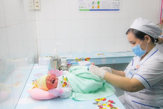 Lấy máu gót chân để tiến hành sàng lọc sơ sinh cho trẻ. Ảnh BVCC