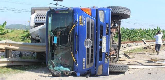 Nghệ An: Mất lái, xe tải húc văng giải phân cách rồi lật ngiêng giữa đường sắt - Ảnh 1.