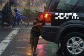 Cậu bé đứng co ro dưới mưa sau đuôi xe ô tô lay động triệu trái tim