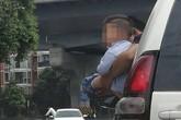 Bé trai được bế ra ngoài cửa ôtô đang chạy để đi vệ sinh