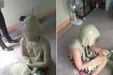 Cô gái trẻ quỳ gối dưới nền đất, trên người dính đầy chất bẩn, nghi bị đánh ghen