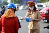 Nữ cảnh sát đội nắng phát khẩu trang ở cửa ngõ Tân Sơn Nhất