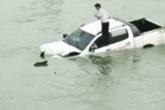 Hình ảnh tài xế trèo lên nóc xe ô tô trôi lềnh bềnh giữa sông khiến nhiều người hoang mang