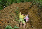 Ông bố đau lòng ôm con gái nhỏ đến nằm thử trong mộ
