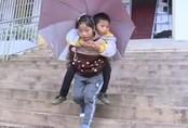 Bé gái 9 tuổi cõng anh trai tật nguyền đến trường mỗi ngày: Câu chuyện lay động hàng triệu trái tim