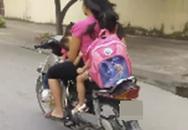 Người mẹ chạy xe máy bằng một tay, một tay bế con bú khiến người đi đường sợ hãi