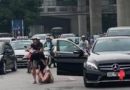Mặc xe cộ đông, cô gái gục đầu ngồi bệt giữa đường bên nam thanh niên và chiếc Mercedes khiến dân tình xôn xao