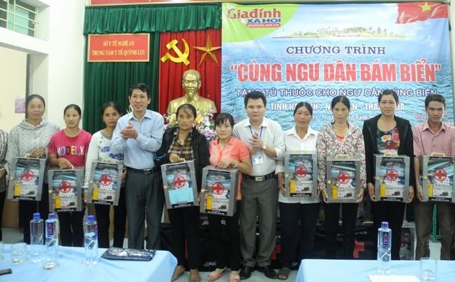 Ông Nguyễn Viết Minh, Trưởng phòng Hành chính - Trị sự, Báo Gia đình và Xã hội (thứ 4 từ trái qua) và ông Lưu Đình Cử, Chánh Văn phòng Sở Y tế Nghệ An (thứ 5 từ phải qua) trao tặng tủ thuốc cho ngư dân Nghệ An