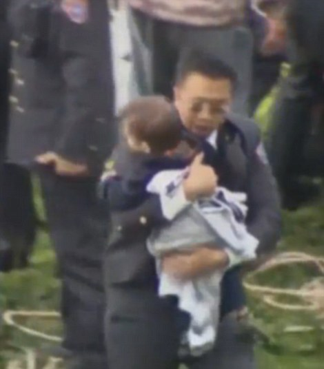 Safe: The toddler and a Taiwanese official rush to safety once they reach dry land, after the little boy is rescued from the plane which crashed into the Keeling River in Taipai, Taiwans capital city