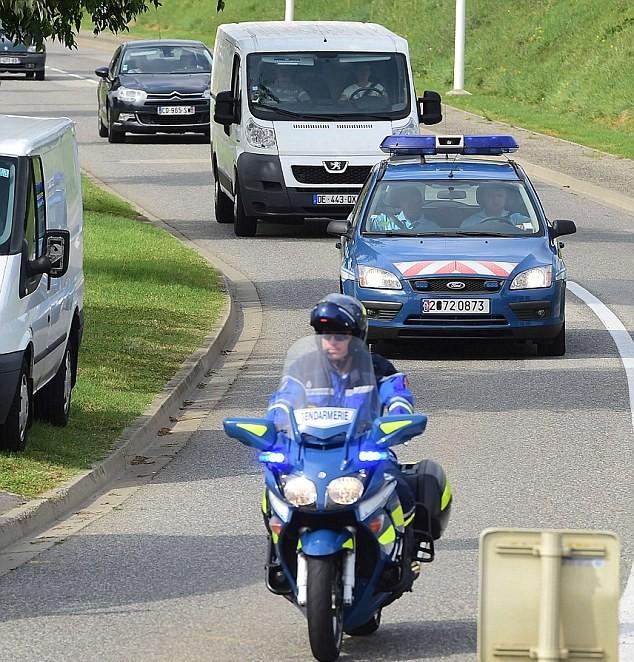 Các nhân viên cảnh sát hộ tống chiếc xe màu trắngđược cho là chở mảnh vỡ từ một máy bay Boeing 777 - có khả năng là từ MH370. Mảnh vỡ này đã được chuyển giao cho một phòng thí nghiệm của Bộ Quốc phòng trong Balma, gần Toulouse, Pháp trước ngày 1/8