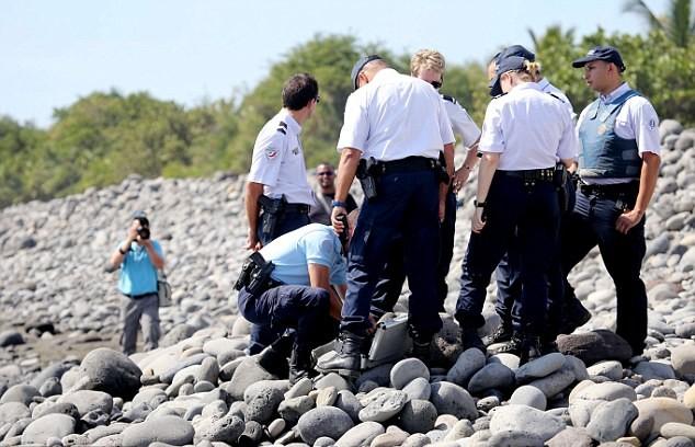 Các nhân viên cảnh sát kiểm tra mảnh vỡ được tìm thấy trên bờ biển đảo của Ấn Độ Dương