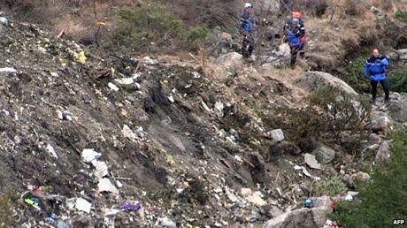 Các nhân viên cứu hộ rà soát hiện trường máy bay rơi.