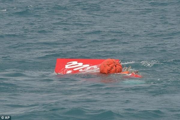 Phần đuôi của máy bay QZ8501 nổi trên mặt nước trong khi thợ lặn đang tiến hành tìm kiếm chiếc hộp đen