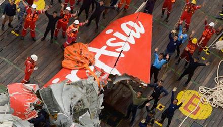 Đội trục vớt đứng cạnh phần đuôi máy bay AirAsia vừa được vớt lên, vẫy trực thăng cứu hộ
