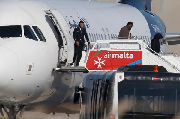 Một số hành khách bắt đầu bước ra khỏi chiếc máy bay bị không tặc. Ảnh: Reuters