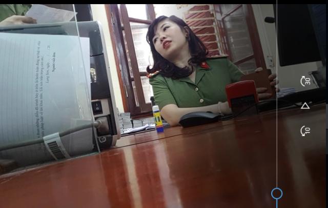 Nữ cán bộ công an tiếp nhận hồ sơ làm thủ tục cấp giấy thông hành giới thiệu chúng tôi nên làm việc với nhân viên công ty cho nhanh.