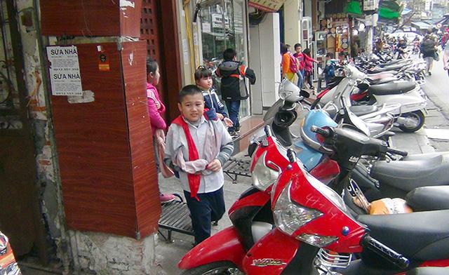 Các em học sinh buộc phải đi bộ dưới lòng đường hoặc luồn lách qua các dãy xe máy để trên vỉa hè.