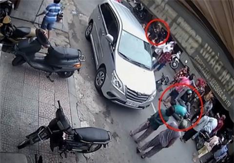 Sau khi gây ra vụ tai nạn giao thông, người đàn ông ngoại quốc (vòng tròn đỏ nhỏ) không biết xử trí thế nào, cũng không giúp đỡ nạn nhân. Người phụ nữ đi cùng xe thì chỉ lo phân bua với những người chứng kiến.