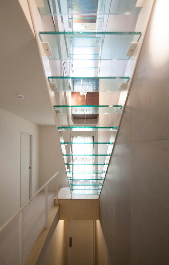 Diện tích khu đất không lớn, xung quanh lại là những ngôi nhà cao tầng, vì thế, sử dụng cầu thang bằng kính ngay dưới giếng trời để thông gió và ánh sáng là lựa chọn vô cùng hợp lý cho công trình.