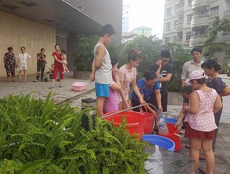 Người dân các tòa nhà chung cư tại Linh Đàm xếp hàng để hứng nước từ dưới mang lên nhà. Ảnh: N.Đ.T