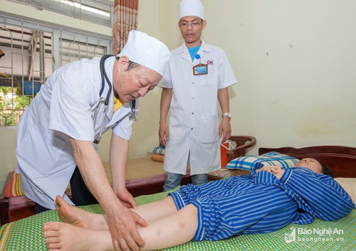 GS.TS Cao Minh Châu - Tổng Thư ký Hội Phục hồi chức năng Việt Nam khám, điều trị cho bệnh nhân tại Bệnh viện PHCN Nghệ An. Ảnh: Thành Cường (Báo Nghệ An).