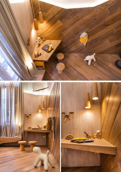 Sàn nhà và 1/2 tường được ốp gỗ. Ở khu vực chiếc bàn học nhỏ, nhà thiết kế sử dụng hai đèn dây ánh sáng vàng. Một chiếc bàn dài, hẹp là cầu nối giữa gường và bàn học. Bé có thể đặt vài cuốn sách, cốc hoặc đồ dùng nhỏ tại đây.